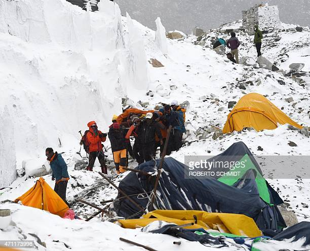In this photograph taken on April 25 rescuers carry a sherpa injured by an avalanche that flattened parts of Everest Base Camp Rescuers in Nepal are...