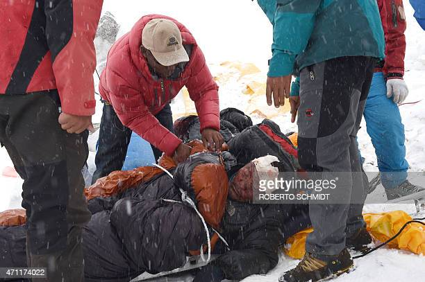 In this photograph taken on April 25 rescuers tend to a sherpa injured by an avalanche that flattened parts of Everest Base Camp Rescuers in Nepal...