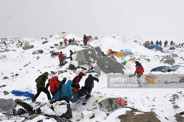 In this photograph taken on April 25 Sherpas climbers porters and rescue teams help carry a person injured by an avalanche that flattened part of...