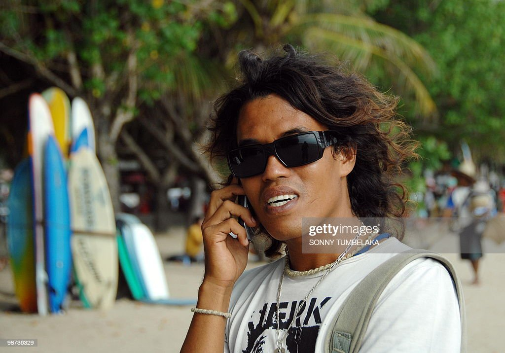 In this photograph taken on April 27, 2010 local surf instructor Rosnan Efendi, 29, talks on a mobile phone in Kuta beach on the resort island of Bali. Fun-loving local beach boys are as much a fixture and, for some women, an attraction of Bali as the sun and surf, but all that could be about to change thanks to a controversial new film. Police have rounded up almost 30 of the so-called beach 'cowboys' in a bid to 'clean up the beach of prostitution', Bali police spokesman Gede Sugianyar said, after documentary 'Cowboys in Paradise' sparked panic among tourism officials. Some of the men at the centre of the brouhaha, like Efendi, who was interviewed for the film, said they were distressed and angry at being hounded as gigolos, and flatly denied offering sexual favours for money.