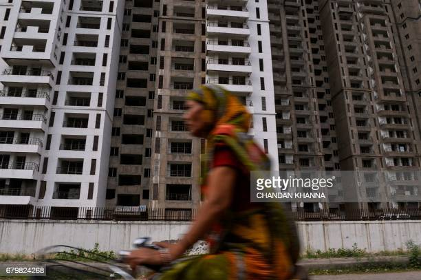 In this photograph taken on April 27 an Indian cyclist rides past incomplete residential apartments in Greater Noida some 25 kilometres southeast of...