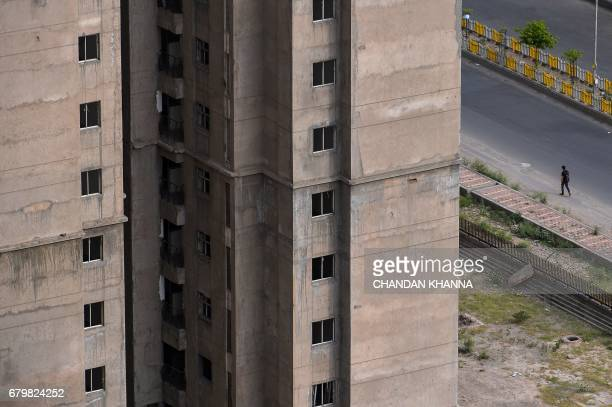 In this photograph taken on April 27 an Indian pedestrian walks past incomplete residential apartments in Greater Noida some 25 kilometres southeast...