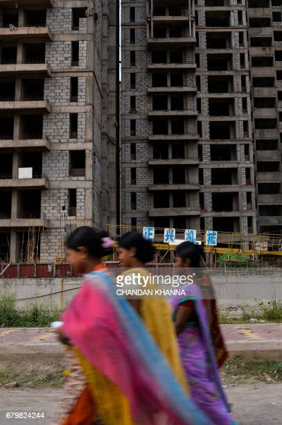 In this photograph taken on April 27 Indian pedestrians walk past incomplete residential apartments in Greater Noida some 25 kilometres southeast of...