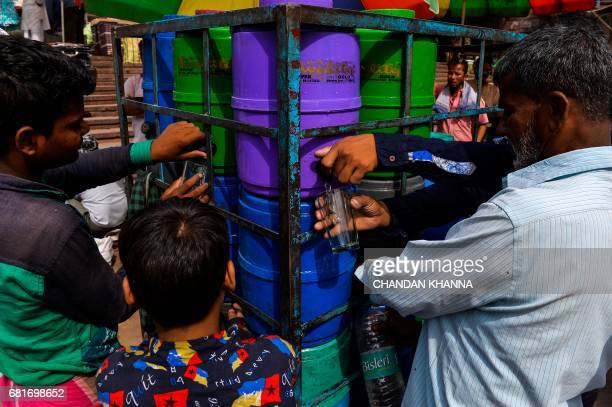 In this photograph taken on April 28 Indian residents take drinking water from containers in New Delhi Shakeel Ahmad wanders the cramped alleyways of...