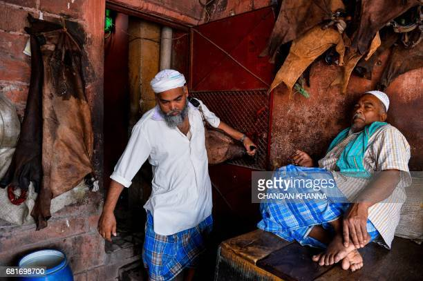 In this photograph taken on April 28 Indian water carrier Shakeel Ahmad leaves a Sufi shrine as he prepares to sell water from a goat skin canteen...
