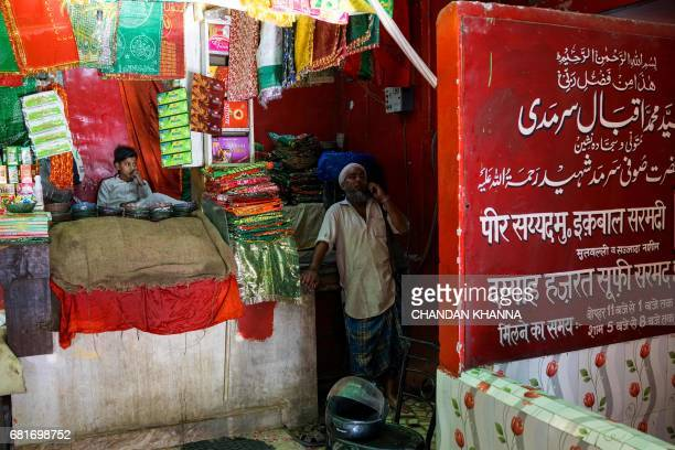 In this photograph taken on April 28 Indian water carrier Shakeel Ahmad speaks on the phone as he stands inside a Sufi shrine near Jama Masjid in New...