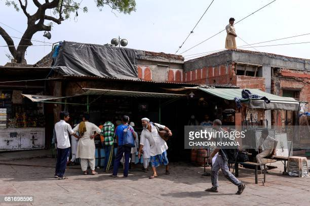 In this photograph taken on April 28 Indian water from a goat skin canteen he carries carrier Shakeel Ahmad leaves a Sufi shrine as he prepares to...