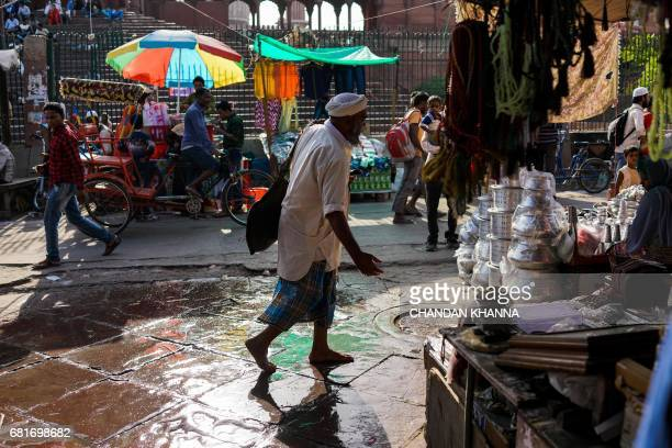 In this photograph taken on April 28 Indian water from a goat skin canteen he carries carrier Shakeel Ahmad walks past Jama Masjid as he sells water...