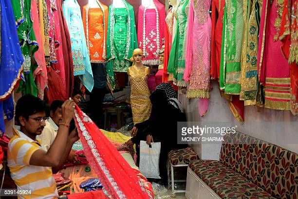 In this photograph taken on April 28 Muslim shoppers sit inside a burqa shop at a market in Bhopal Only three words were scrawled on the letter from...