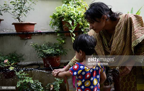 In this photograph taken on April 28 Sadaf Mehmood and her threeyearold daughter Maisha water plants at her house in Bhopal Only three words were...