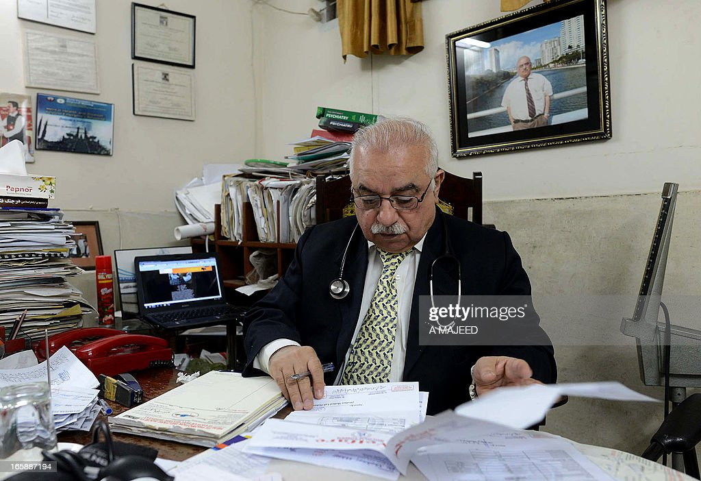 In this photograph taken on April, 5 2013, Pakistani psychiatrist Mian Iftikhar Hussain , looks over patient files at his private clinic in Peshawar. After nine friends and relatives were killed in a US drone strike four years ago, Mohammed Fahim took tranquilisers to blot out the nightmares, one of a growing number of Pakistanis suffering from conditions related to depression, anxiety and mental health problems because of war. AFP PHOTO/ A MAJEED