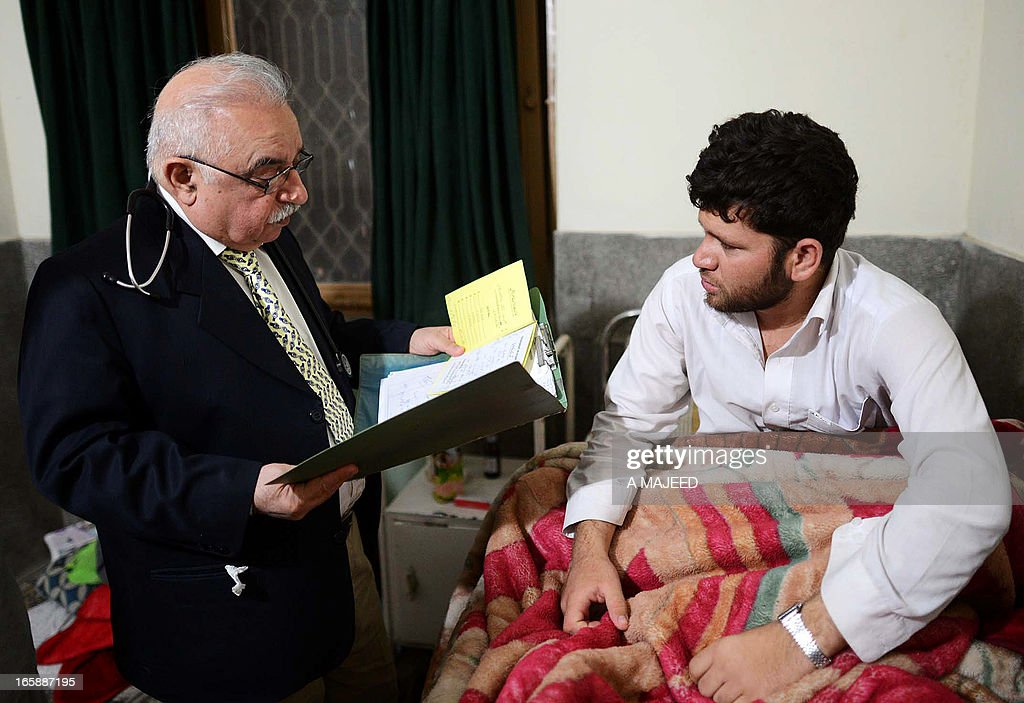 In this photograph taken on April, 5 2013, Pakistani psychiatrist Mian Iftikhar Hussain (L), speaks with a patient at his private clinic in Peshawar. After nine friends and relatives were killed in a US drone strike four years ago, Mohammed Fahim took tranquilisers to blot out the nightmares, one of a growing number of Pakistanis suffering from conditions related to depression, anxiety and mental health problems because of war. AFP PHOTO/ A MAJEED