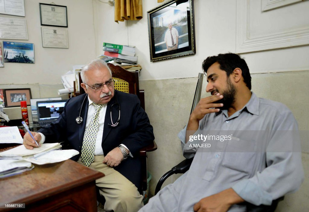 STORY 'PAKISTAN-US-UNREST-MISSILE-HEALTH, FEATURE' BY GUILLAUME LAVALLEE In this photograph taken on April, 5 2013, Pakistani psychiatrist Mian Iftikhar Hussain (L), speaks with a patient at his private clinic in Peshawar. After nine friends and relatives were killed in a US drone strike four years ago, Mohammed Fahim took tranquilisers to blot out the nightmares, one of a growing number of Pakistanis suffering from conditions related to depression, anxiety and mental health problems because of war.