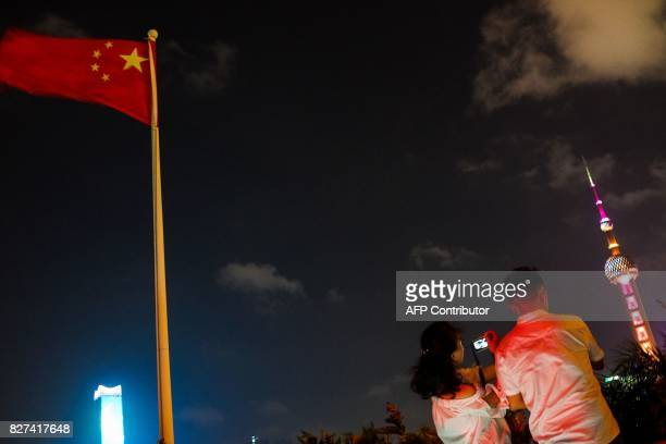 In this photograph taken on August 1 a Chinese couple takes picture from a club on the Bund along the Huangpu River at the Bund in Shanghai A wildly...