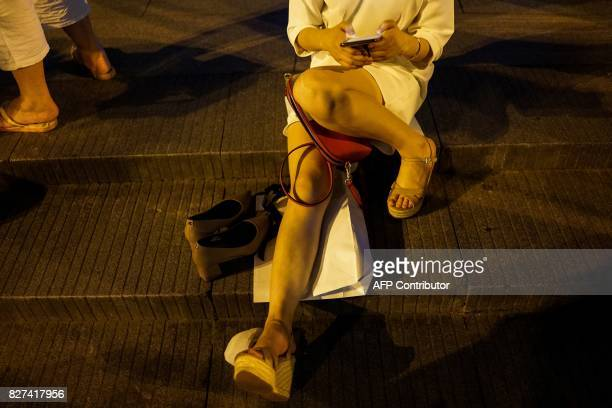In this photograph taken on August 1 a Chinese woman looks at her phone on the Bund along the Huangpu River at the Bund in Shanghai A wildly popular...