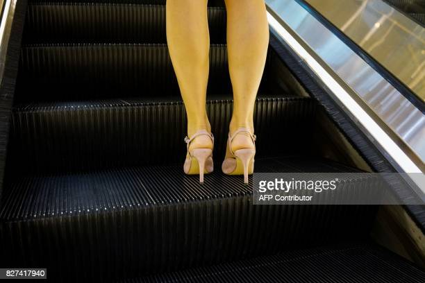 In this photograph taken on August 1 a Chinese woman uses an escalator in the Lujiazui Financial District in Pudong in Shanghai A wildly popular...