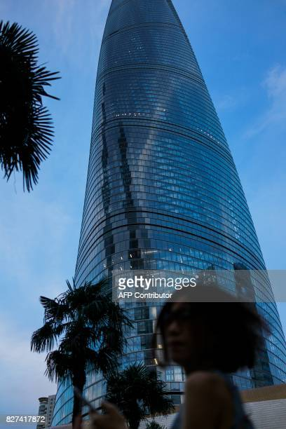 In this photograph taken on August 1 a Chinese woman walks in the Lujiazui Financial District in Pudong in Shanghai A wildly popular drama likened to...