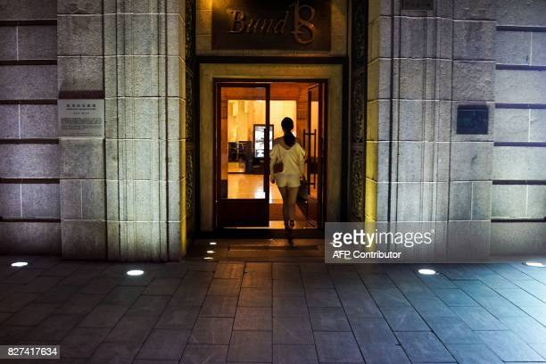 In this photograph taken on August 1 a Chinese woman walks into a club on the Bund along the Huangpu River at the Bund in Shanghai A wildly popular...