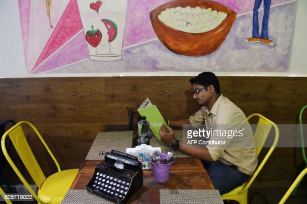 In this photograph taken on August 1 a man looks at a menu next to a decorative typewriter in a restaurant in Mumbai The unmistakable chatter of...