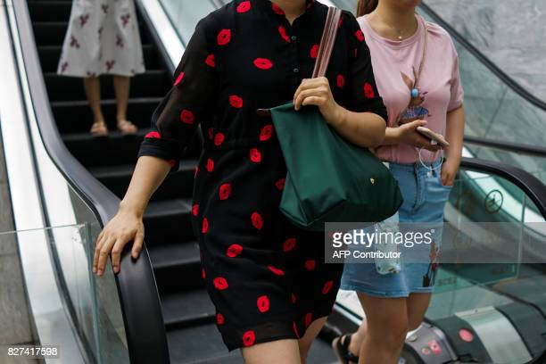 In this photograph taken on August 1 Chinese women descend from an escalator in the Lujiazui Financial District in Pudong in Shanghai A wildly...