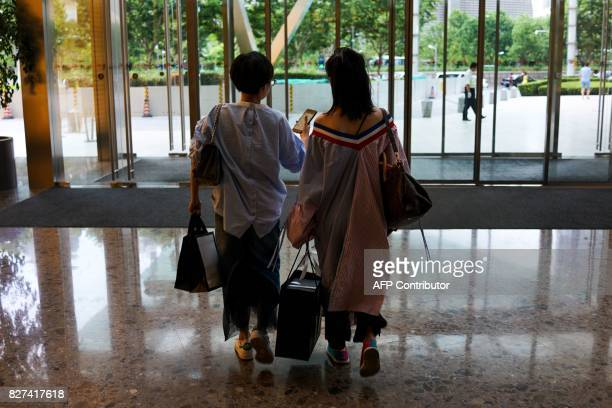 In this photograph taken on August 1 Chinese women walk out of a shopping centre at the Lujiazui Financial District in Pudong in Shanghai A wildly...