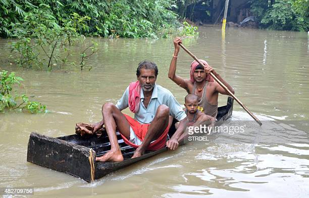 In this photograph taken on August 1 Indian villagers paddle a small boat through floodwaters in Bherampur Block Murshidabad District some 220kms...