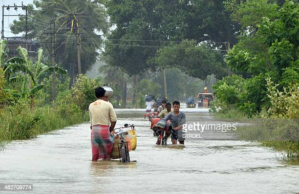 In this photograph taken on August 1 Indian villagers wade through floodwaters in Bherampur Block Murshidabad District some 220kms north of Kolkata...