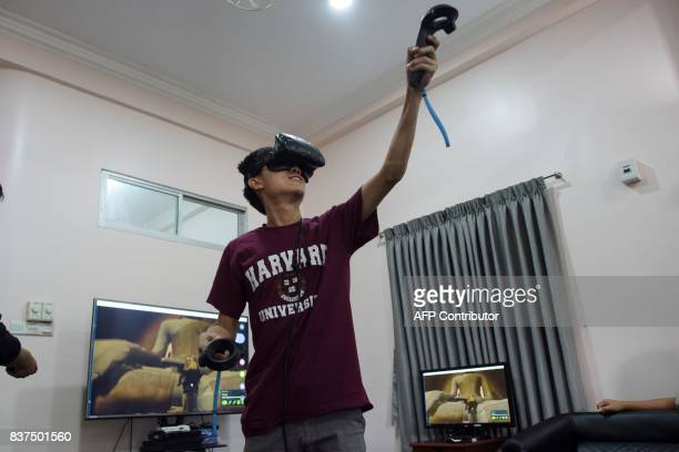 In this photograph taken on August 11 a man wears a VR goggles as he watches some of the 360 4K video footage that a specialized company recorded at...