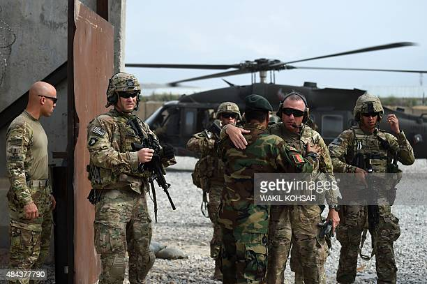 DECAMME In this photograph taken on August 12 US and Afghan National Army personnel greet each other at coalition force Forward Operating Base...