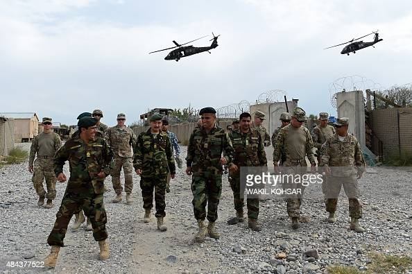 In this photograph taken on August 13 US army and Afghan National Army soldiers walk as a NATO helicopter flies overhead at coalition force Forward...