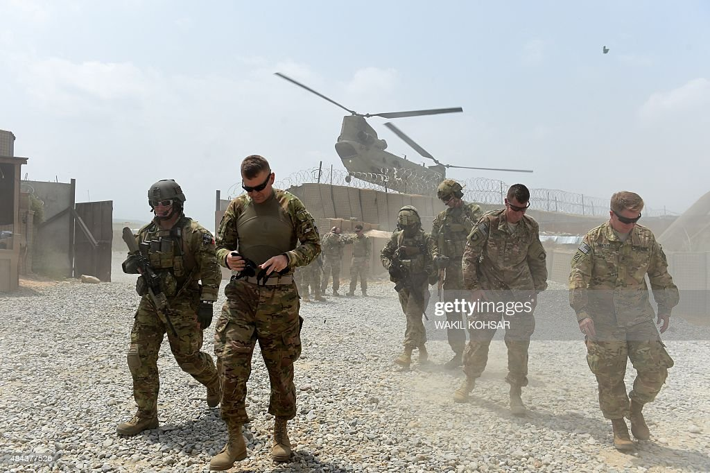 In this photograph taken on August 13 US army soldiers walk as a NATO helicopter flies overhead at coalition force Forward Operating Base Connelly in...