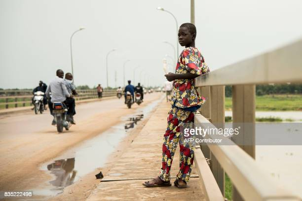 In this photograph taken on August 15 a child eats sweet potato as he stands on the bridge which spans the River Chari in the Chadian capital of...