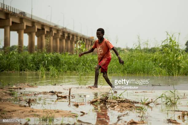 In this photograph taken on August 15 a child plays in the waters of the River Chari in the Chadian capital of N'Djamena close to the border with...