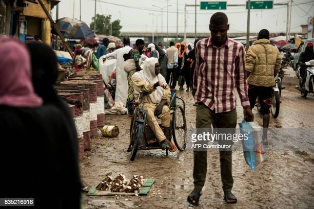 In this photograph taken on August 15 a disabled man sits in a wheelchair as he asks for money from pedestrians in a market in the Chadian capital of...
