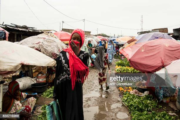 In this photograph taken on August 15 a pedestrian covers her face as she walks through a market in the Chadian capital of N'Djamena / AFP PHOTO /...