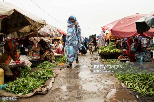 In this photograph taken on August 15 a pedestrians walk past vendors in a muddy area of a market in the Chadian capital of N'Djamena / AFP PHOTO /...