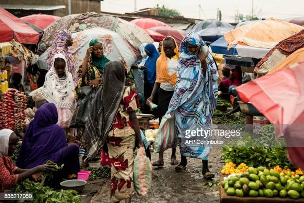 In this photograph taken on August 15 pedestrians walk past vendors as they pass through a market in the Chadian capital of N'Djamena / AFP PHOTO /...