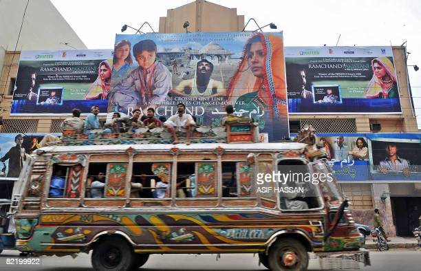 KEMP 'ENTERTAINMENTPAKISTANINDIAFILMPOLITICS' In this photograph taken on August 2 2008 Pakistani men sit on a bus driving past a cinema displaying a...