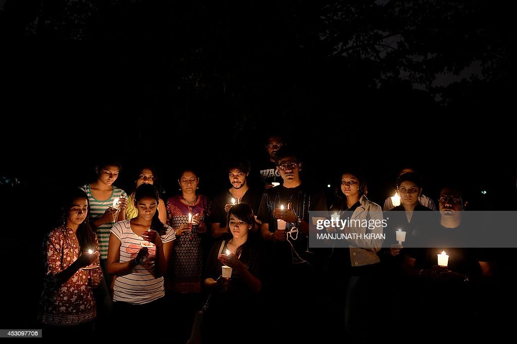 In this photograph taken on August 2, 2014 young Indian activists calling themselves 'concerned citizens' arrive to take part in a candle light vigil in protest against the recent rape of a 6-year-old girl in a school in Bangalore. The child was allegedly assaulted in a classroom of the school, a top fee-paying institution favoured by local politicians and businessmen. Police said the girl had complained of the July 2 attack to a teacher, but the school had failed to inform her parents who only learned of the incident a week later when she shared details with them. AFP PHOTO/Manjunath KIRAN