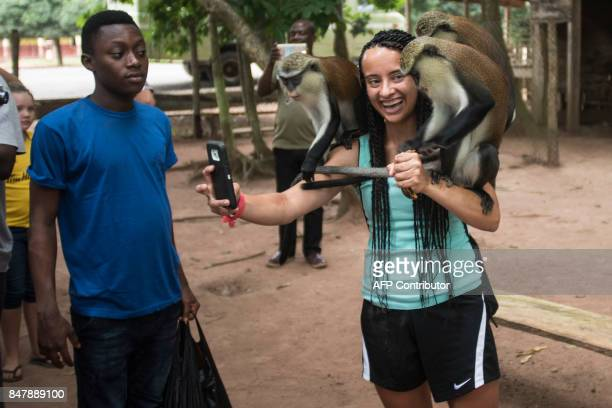 In this photograph taken on August 22 visitors take 'selfies' with monkeys at The Tafi Atome Monkey Sanctuary in the Volta Region of Ghana / AFP...