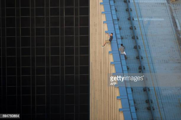 TOPSHOT In this photograph taken on August 23 two men take a series of selfies as they sit on the ledge of a highrise building in an activity called...