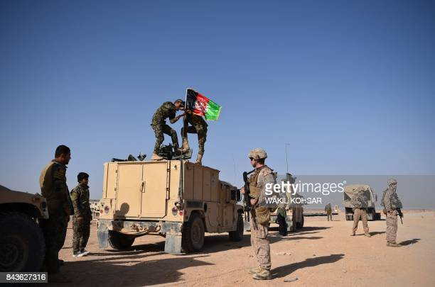 In this photograph taken on August 28 a US Marine looks on as Afghan National Army soldiers raise the Afghan National flag on an armed vehicle during...