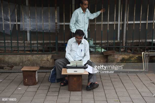 In this photograph taken on August 3 a petitioner waits as a typist prepares his petition outside a city court in Mumbai The unmistakable chatter of...