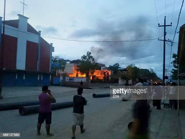 In this photograph taken on August 31 Indian people watch a blaze at the residence of Manipur state health minister Phungzaphang Tonsimg which was...