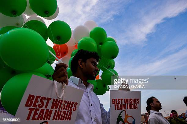 In this photograph taken on August 5 an Indian man carries balloons in the colour of the Indian flag at a ceremonial event to support the Indian...