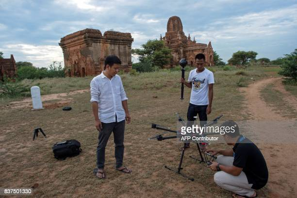 In this photograph taken on August 5 Nyi Lin Seck and two members of his team stand next to a drone carrying a 3604K video camera with which they are...