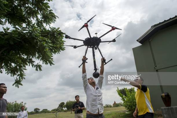 In this photograph taken on August 5 Nyi Lin Seck reaches to grab a drone carrying a 3604K video camera after flying it over the ancient city of...