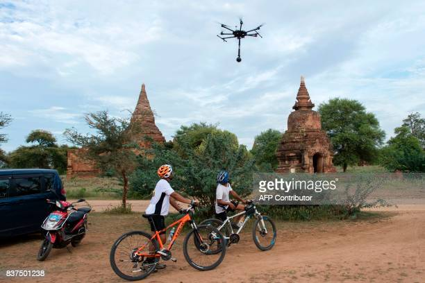 In this photograph taken on August 5 two tourists watch as a drone carrying a 3604K video camera flies low documenting the crumbling 700yearold walls...