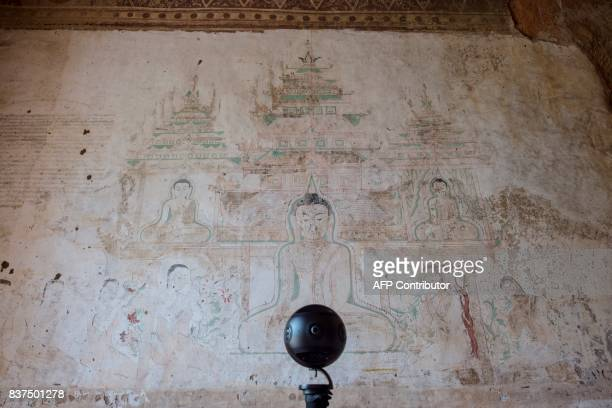 In this photograph taken on August 6 a 3604K video camera records a fading mural in the crumbling 700yearold walls of the ancient city of Bagan Few...