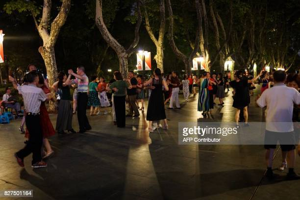 In this photograph taken on August 6 Chinese men and women dance in a public park in Shanghai / AFP PHOTO / Chandan KHANNA